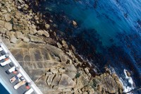 Ocean, rocks, and deck chairs from above [1101220499]