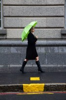 Woman walking with green umbrella [1112223499]