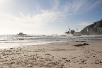 Stranded ship on Clifton beach with tugboat [1205128283]