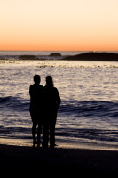 Silhouette of two people talking on the beach at sunset [1304045090]