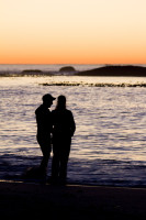 Silhouette of two people talking on the beach at sunset [1304045092]