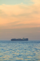 An orange sky with a cargo ship at sea [1304055230]