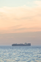 An orange sky with a cargo ship at sea [1304055233]