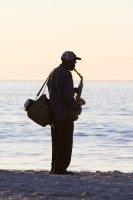 Saxophonist silhouette on the beach [1304125385]