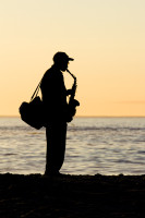 Saxophonist silhouette on the beach [1304125389]