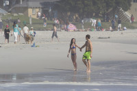 Man an woman holding hands on the beach [1308046997]